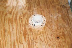 Toilet drain with wood ''floor donut'' to keep tile away.