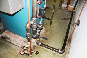 The boilers drain pipe. The pipe standing vertical in the background swings down over a floor drain when needed.